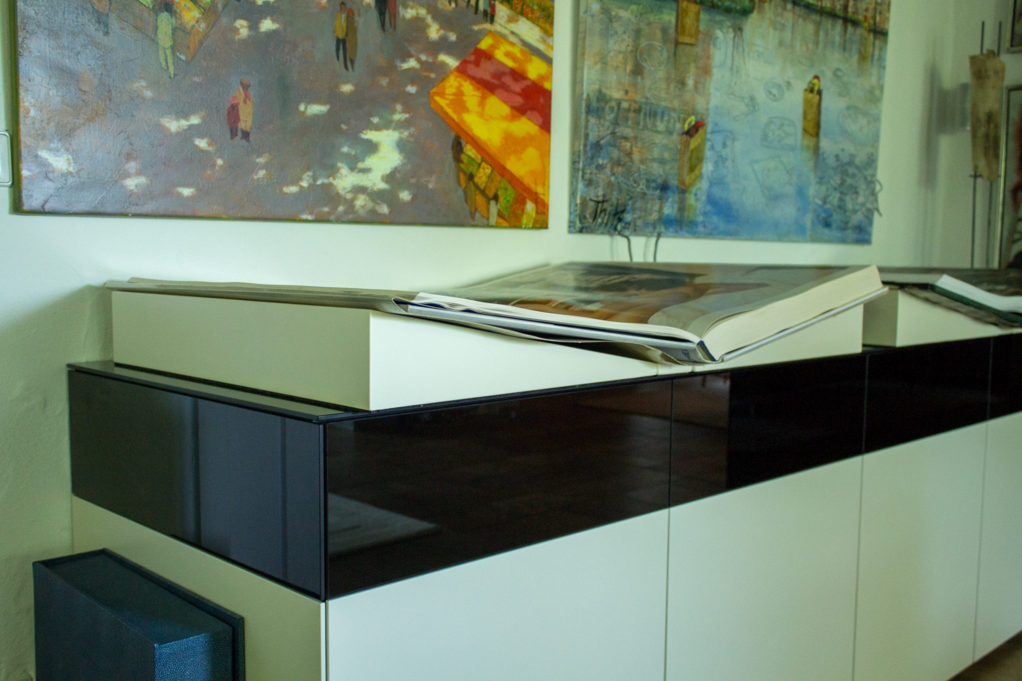 Aufgeschlagene übergroße Bücher, die auf einem schwarz-weißen Schränkchen liegen. Die Buchstützen sind von der Schreinerei maßgefertigt.