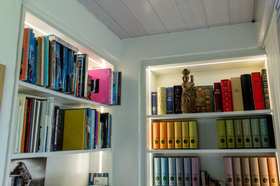 Sonderanfertigung eines weißen Bücherregal mit eingefassten LED Streifen in modernem Look.