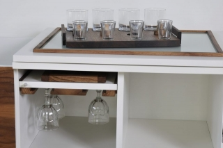 Ein moderner, offener Barschrank, mit speziellen Glashalterungen aus Massivholz. Auf dem Schrank steht ein Massivholz Tablett, das auch Einlassungen für Gläser hat.