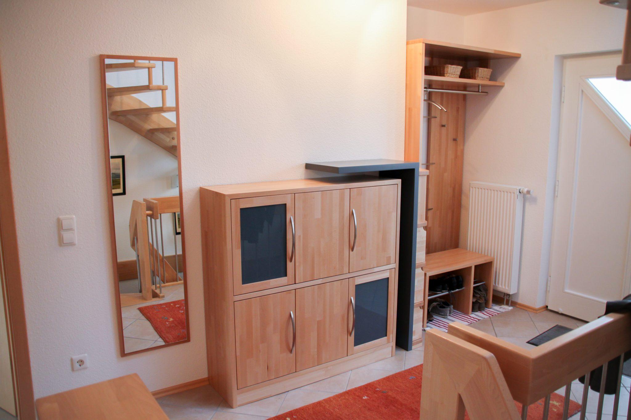 Eine maßgefertigte Garderobe aus Buche-Massivholz, die in einem hellen modern eingerichteten Flur mit vielen Holzelementen steht.