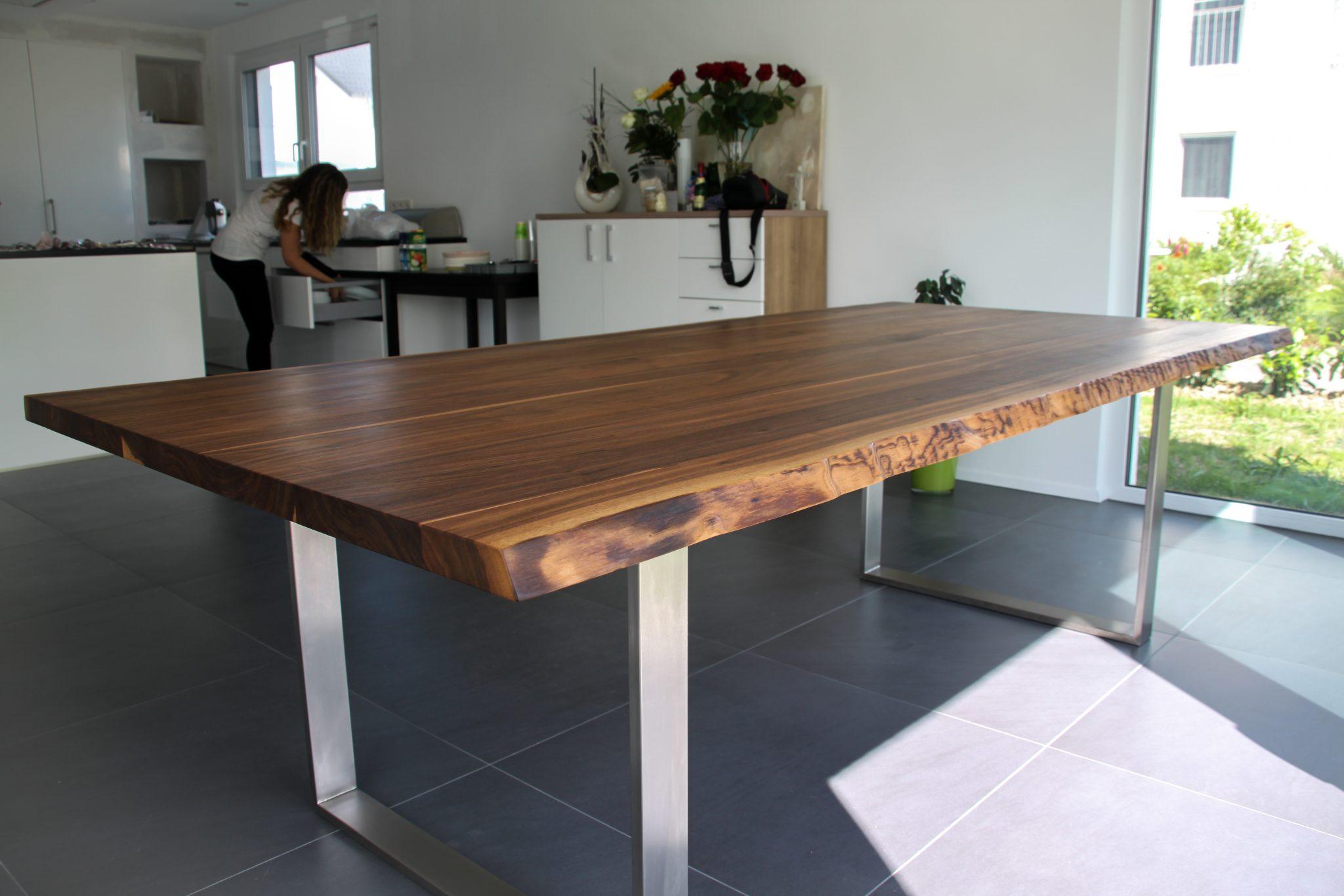 Massiver Nussbaumtisch mit Waldkante und Edelstahl-Füßen, der in einer modernen, hellen Wohnung mit offener Küche steht.