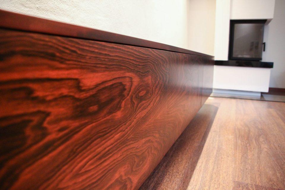 Nahaufnahme entlang der maserfurnierten Front eines niedrigen Sideboard aus dunklem Tropenholz.