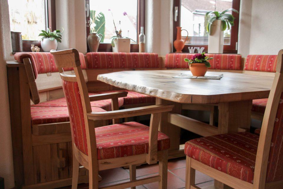 Eine rustikale Erker-Bank mit Tisch und Stühlen, gefertigt aus Wildeiche