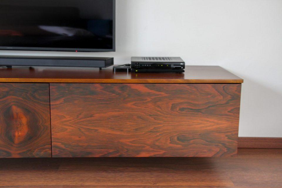 An einer Wand schwebender, niedriger TV-Schrank aus Palisander. Auf dem Schrank steht ein moderner Fernseher.