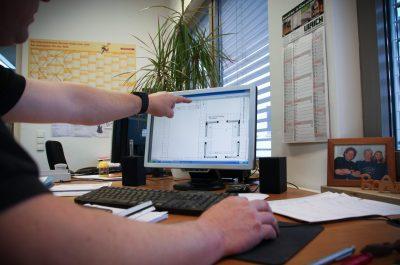 Schreinerei Mitarbeiter für den Bereich Kundenkontakt, der mit dem Zeigefinger auf eine PC Bildschirm zeigt.