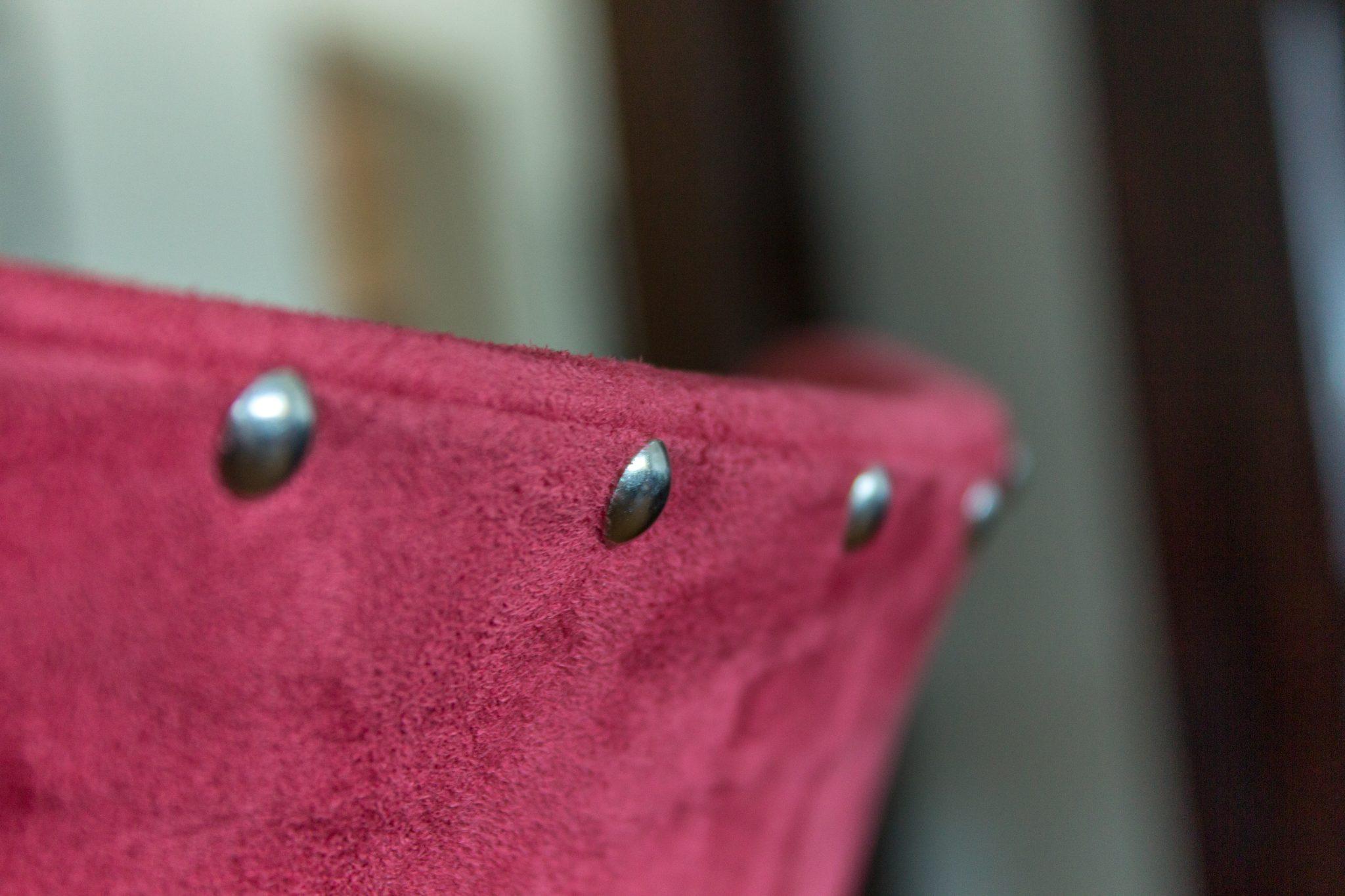 Nahaufnahme von Polster-Nägeln in einem roten Echt-Lederbezug einer Rückenlehne.