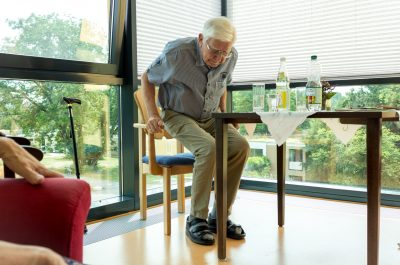 Älterer Herr, der aus einem von der Tischlerei angefertigten Sondermöbelstück mit nach Maß erhöhter Armlehne aufsteht.