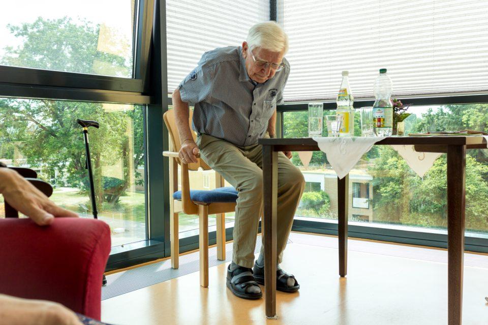 Älterer Herr im Seniorenheim setzt sich gerade hin. Der Stuhl wurde individuell für ihn nach Maß und mit erhöhten Armlehnen gefertigt.