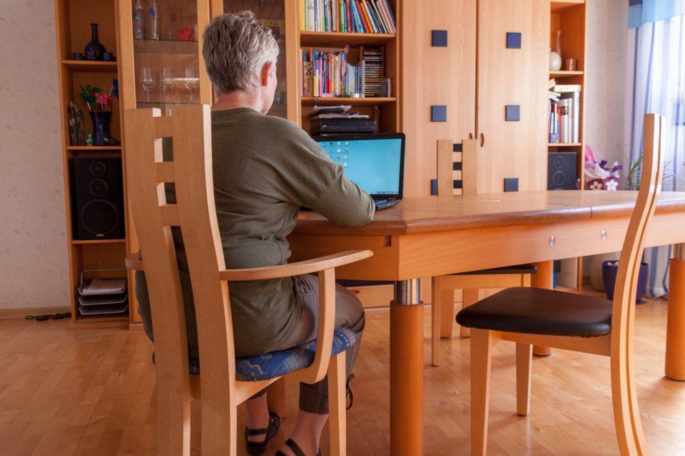 Eine Frau, die auf einem Massivholzstuhl aus der Xen- Serie sitzt und an einem Laptop arbeitet.