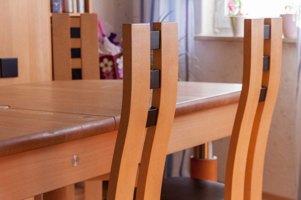 Detailaufnahme der leicht gebogenen Rückenlehne zweier Stühle aus der Xen-Serie der Schreinerei. Die Stuhle stehen an einem Holztisch in passender Optik.