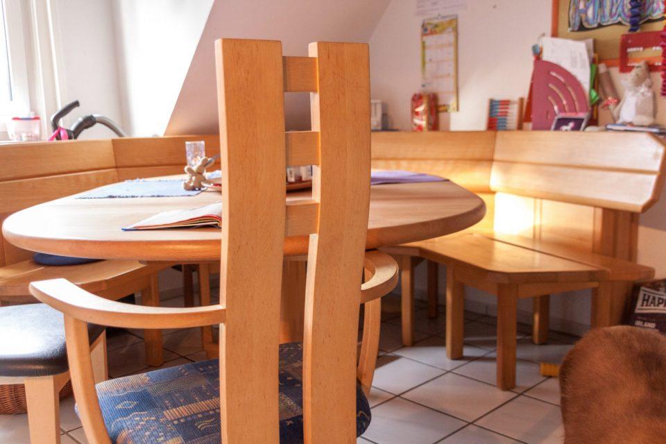Nahaufnahme eines Stuhles aus hellem Holz, der an einem Tisch mit Eckbank steht.